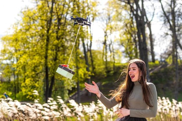An einem sonnigen und windigen tag erhält eine junge lächelnde emotionale brünette ein überraschungsgeschenk von quadcopter