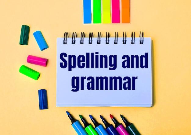 An einer beigen wand ein notizbuch mit den worten rechtschreibung und grammatik, helle filzstifte und aufkleber