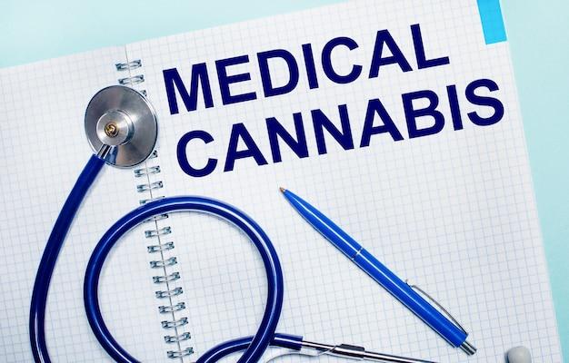 An einer hellblauen wand ein offenes notizbuch mit den worten medical cannabis, ein blauer stift und ein stethoskop. sicht von oben.