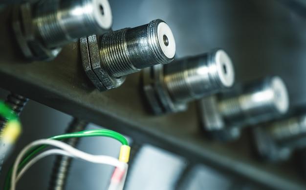 An einer metallhalterung hängen bei der herstellung von sondergeräten reihen von metallrundsteckern, die durch drähte miteinander verbunden sind. industrielles unternehmenskonzept