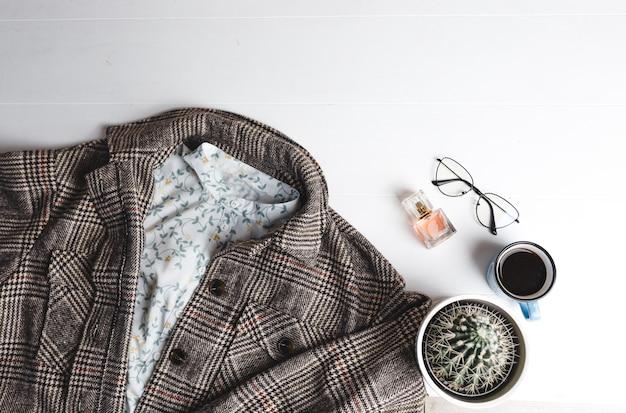 An einer weißen wand liegen die strickjacke einer frau, eine tasse kaffee, ein kaktus, eine brille und das parfüm einer frau