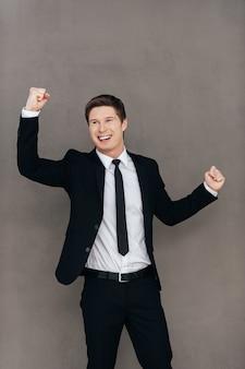 An erfolg gewöhnt. glücklicher junger mann in formeller kleidung, der vor grauem hintergrund gestikuliert und lächelt