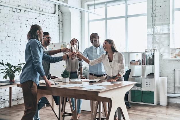 An unser team! gruppe glücklicher geschäftsleute, die sich gegenseitig anstoßen und lächeln, während sie im sitzungssaal stehen
