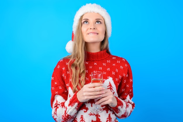 An weihnachten werden träume wahr! porträt des glücklichen aufgeregten fröhlichen freudigen verträumten mädchens mit langen blonden haaren, die lippen beißen und einen wunsch machen, lokalisiert auf hellblauem hintergrund