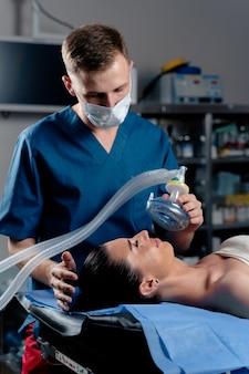 Anästhesist, der ingalationsanästhesie für patienten macht. arzt legt dem patienten eine maske auf, bevor er mit der operation beginnt