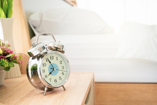 Analoger wecker auf dem holztisch im schlafzimmer