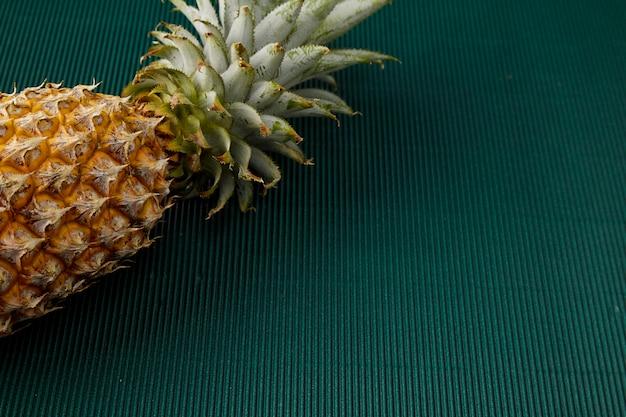 Ananas auf grünem papierhintergrund