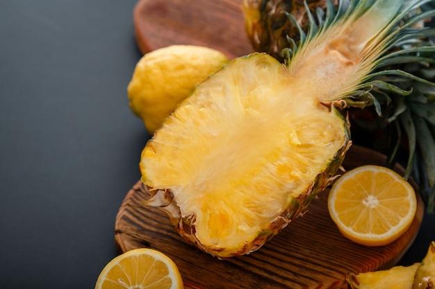 Ananas auf schneidebrett. frische süße halbgeschnittene ananas. geschnittene tropische früchte der ananas, die mit zitruszitronen auf dunklem schwarzem hintergrund des sommers mit kopienraum geschnitten werden.