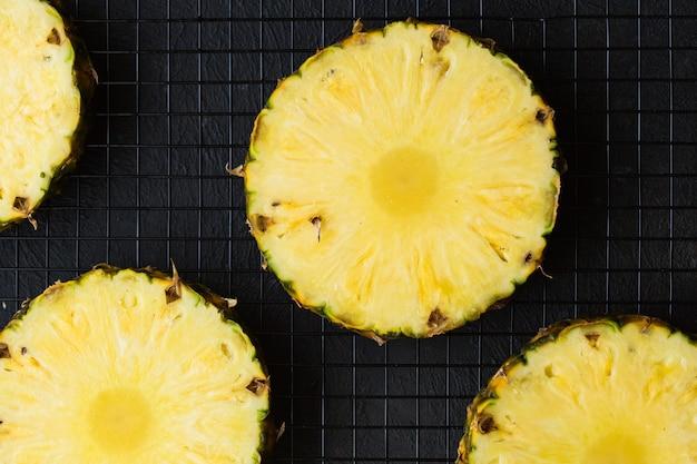 Ananas auf schwarzem betontisch. ganze und geschnittene tropische ananas mit kopierraum. flach liegen
