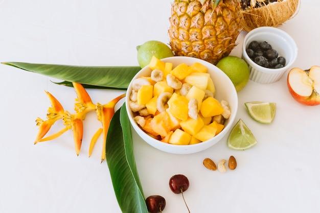 Ananas; bananen- und apfelsalat in der weißen schüssel mit zitronen
