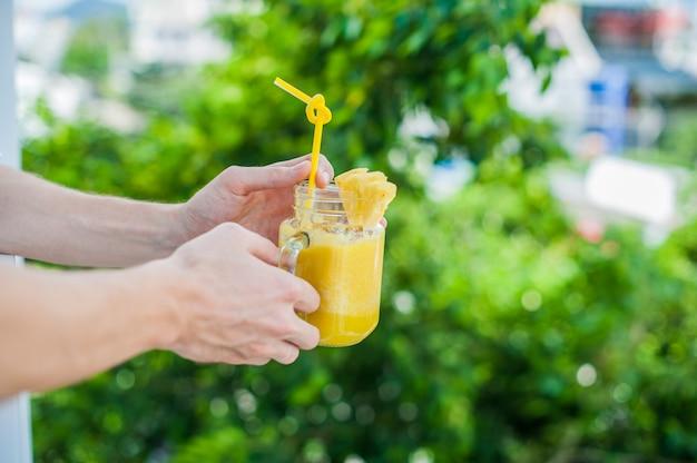 Ananas-cocktail mit einer scheibe in den händen mann auf der terrasse. tropisches konzept
