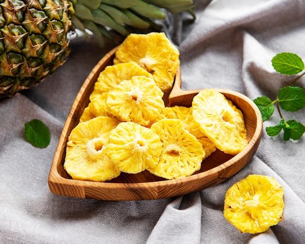 Ananas getrocknete ringe auf grauem textilhintergrund