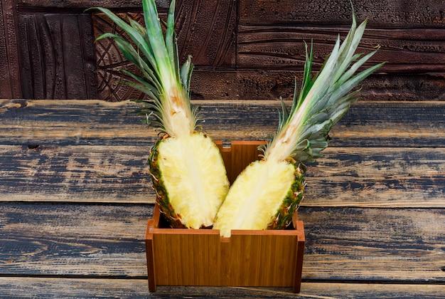Ananas halbiert in einer holzplatte auf alten holz- und dunklen steinfliesen, seitenansicht.