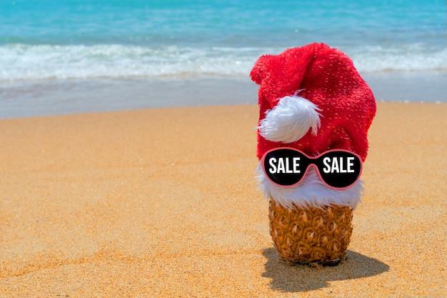 Ananas im weihnachtsmannhut auf gläsern mit textverkauf am tropischen strand. schwarzer freitag