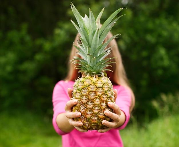 Ananas in den händen einer schönen frau