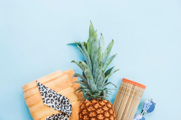 Ananas in der nähe von handtuch und matte mit sonnenbrille