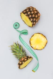 Ananas in stücke schneiden und maßband. grauer hintergrund. flach legen