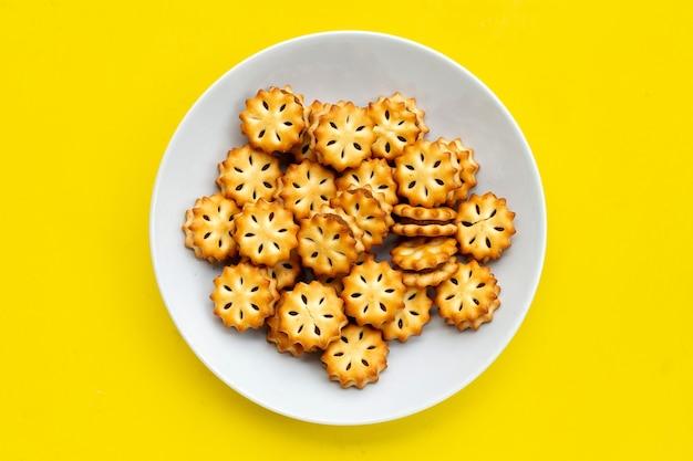 Ananas-kekse in weißer platte auf gelbem hintergrund.