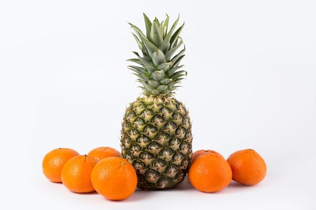 Ananas mandarinen frische reife milde saftige ganze leckere früchte auf einem weißen