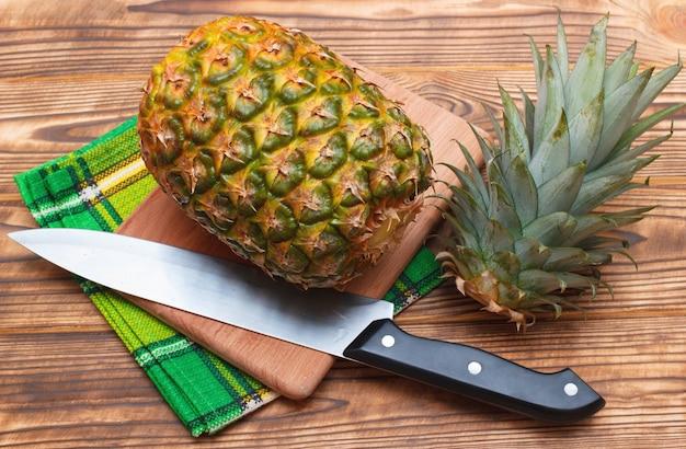 Ananas mit geschnittener spitze auf hölzernem hintergrund