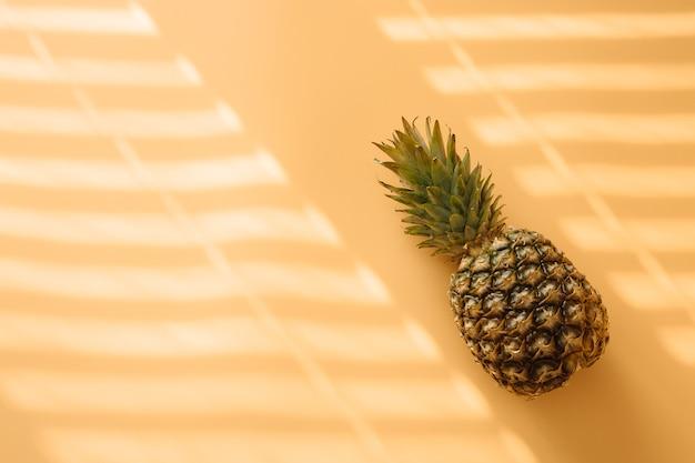 Ananas mit hartem trendigem schatten auf pastellgelbem hintergrund.