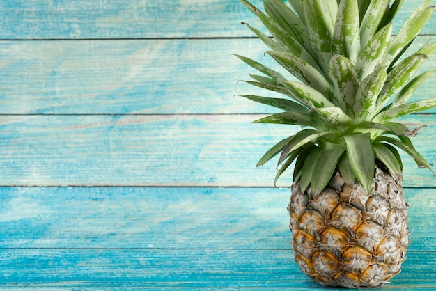Ananas mit kopienraum auf hölzernem hintergrund