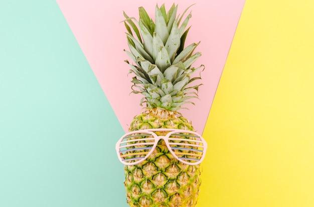 Ananas mit sonnenbrille auf dem tisch