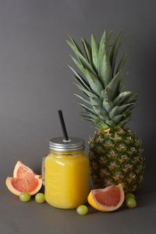 Ananas oder fruchtsaft gläser mit früchten - ananas, orangen, grapefruit, limette und trauben.
