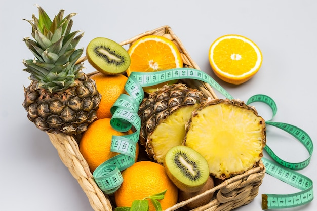 Ananas, orange und kiwi im rattankorb geschnitten. maßband auf obst. grauer hintergrund. ansicht von oben
