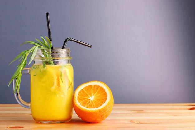 Ananas-orangen-cocktail. alkoholfreie zitrus-sommergetränke auf holztisch