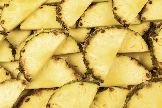 Ananas saftige gelbe scheiben hintergrund. ansicht von oben.