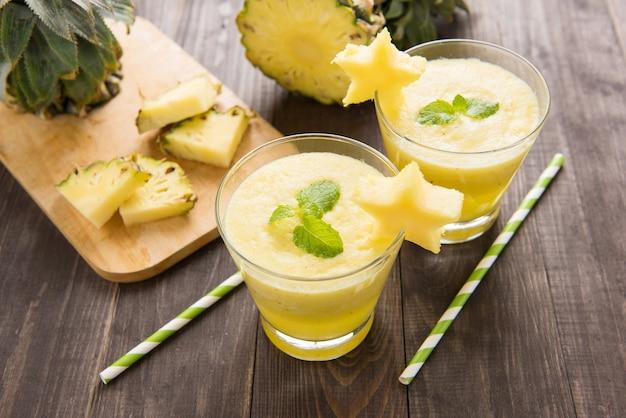 Ananas smoothie mit frischer ananas auf holztisch