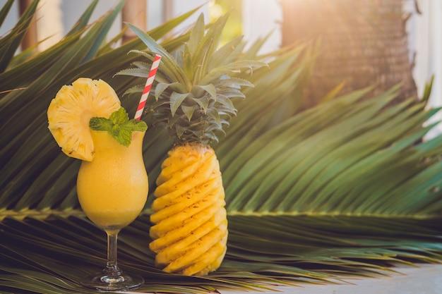 Ananas und ananas-smoothies gegen die oberfläche eines palmenzweigs