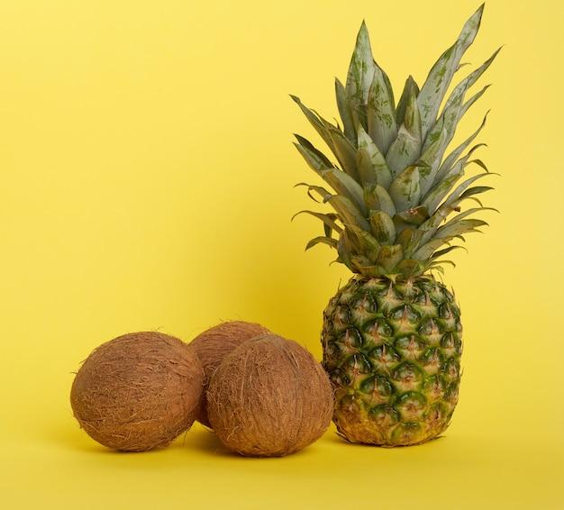 Ananas und ganze braune kokosnüsse auf gelbem hintergrund, gesunde früchte