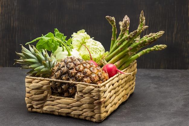 Ananas und gemüse im rattankorb. schwarzer hintergrund. platz kopieren
