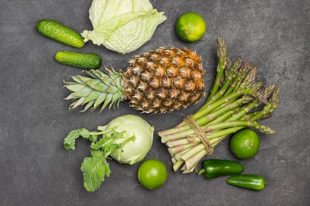 Ananas und grüner spargel im bündel auf dem tisch gebunden. kohlrabi, wirsing und limette. schwarzer hintergrund. flach legen