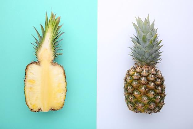 Ananas und hälfte der ananas auf einem bunten hintergrund