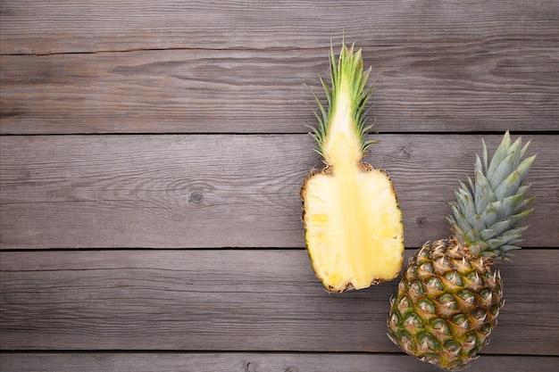 Ananas und hälfte der ananas auf einem grauen hintergrund