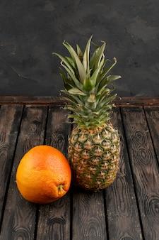 Ananas und orange frisch reif saftig auf einem holzschreibtisch