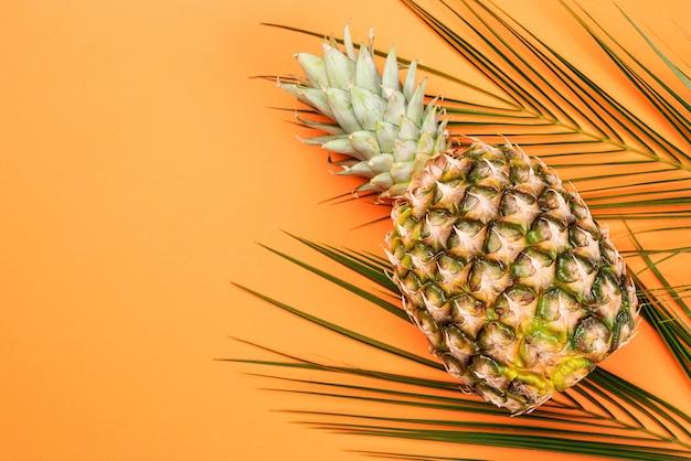 Ananas und tropische palmblätter auf orangem hintergrund. kreative flache lage mit kopienraum.