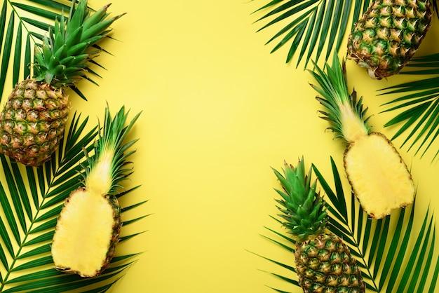 Ananas und tropische palmblätter auf schlagkräftigem gelbem pastellhintergrund. sommer-konzept