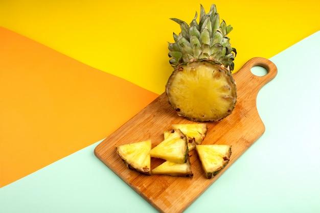 Ananas weich saftig reif auf einem hölzernen braunen schreibtisch und auf einem bunten boden