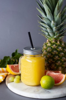 Ananascocktail oder -saft im glas und in den früchten - ananas, orangen, pampelmuse, kalk und trauben.