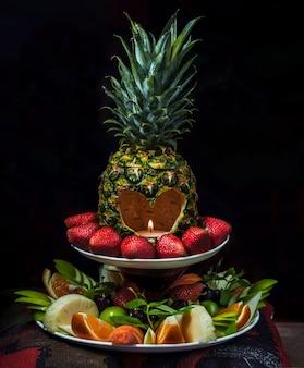 Ananaskorb geschnitten und kerze wird innen auf einen obstteller gelegt