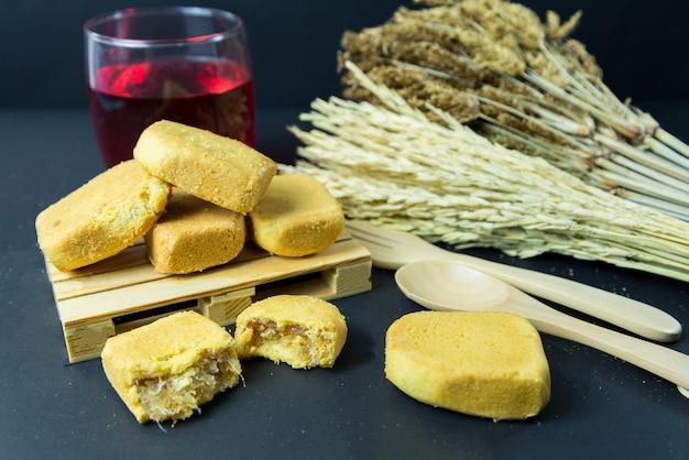 Ananaskuchen oder ananasgebäckkuchen mit ananasmarmelade auf kleiner hölzerner palette. süßes traditionelles taiwanesisches gebäck, das butter enthält. obst. dessert.