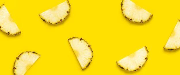 Ananasscheibe gegen auf gelbem hintergrund. ansicht von oben, flach. banner.