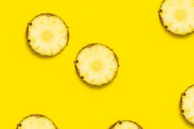 Ananasscheibe gegen auf gelbem hintergrund. ansicht von oben, flach.