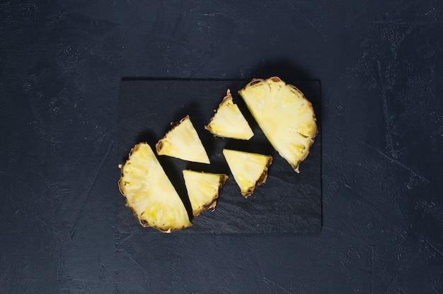 Ananasscheiben auf schwarzem steinbrett mit raum für text