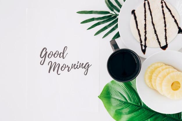 Ananasscheiben; tortillas und kaffee auf blättern mit guten morgen text auf papier auf weißem hintergrund