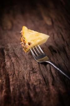 Ananasscheiben und -ananas schälten asiat-art auf dem alten hölzernen hintergrund
